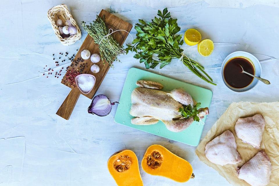 Bord med hel kylling, urter, hvidløg, rødløg og citron.