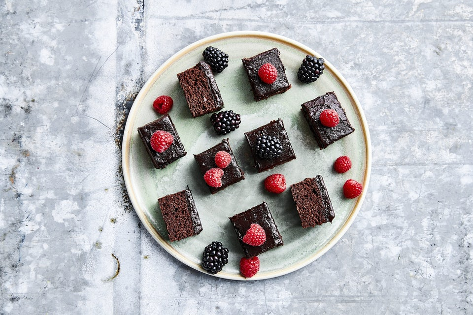 Tallerken med stykker af chokoladekage og hindbær