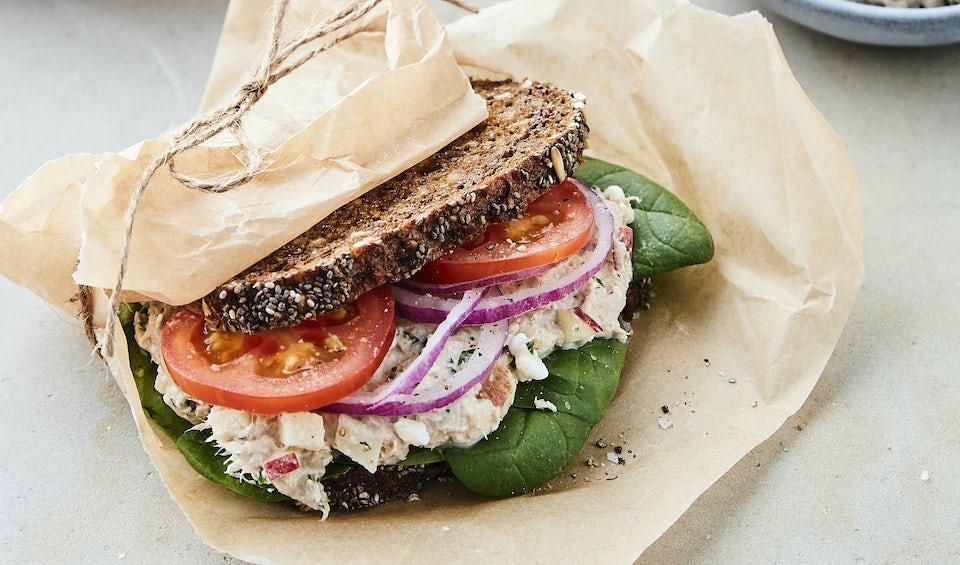 Sandwich af rugbrød med tunsalat pakket ind i papir