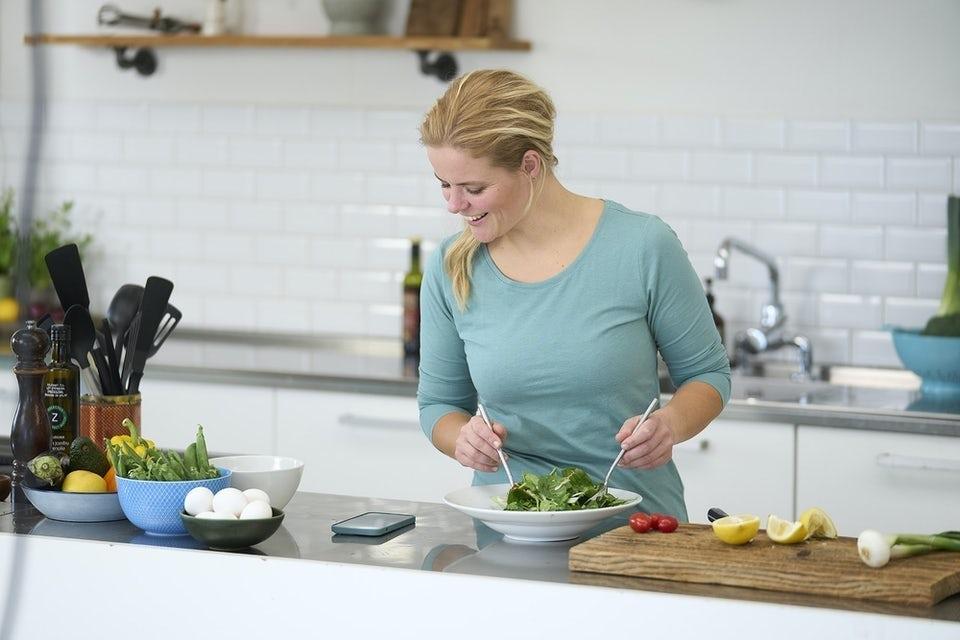 Kvinde laver mad I køkken