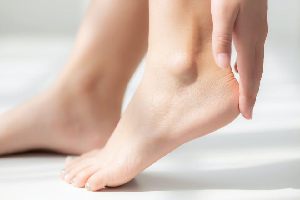 Kvinde smører creme på hælrevner.