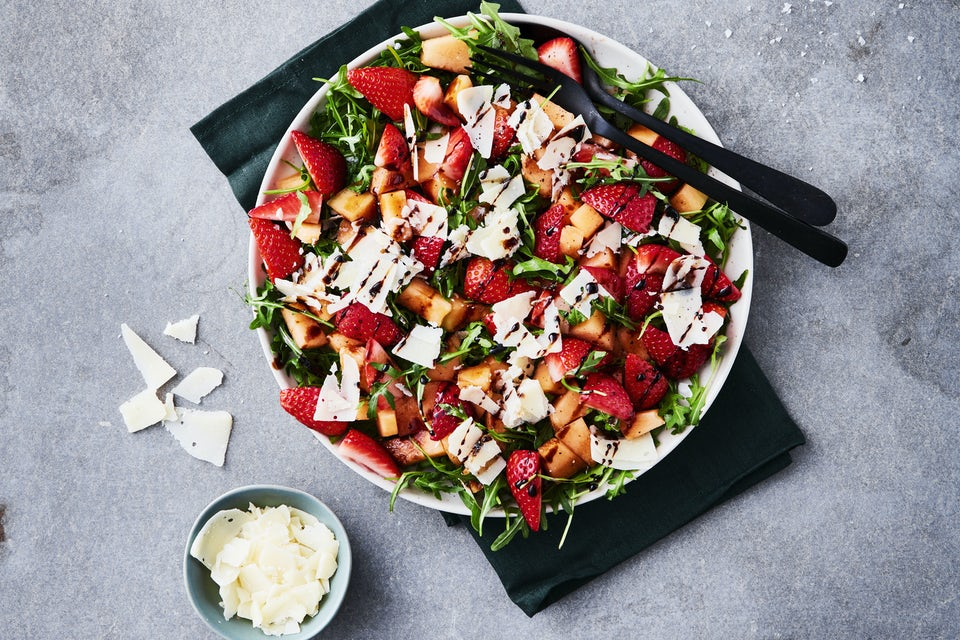 Skål med salat af melon, jordbær, rucola og parmesan