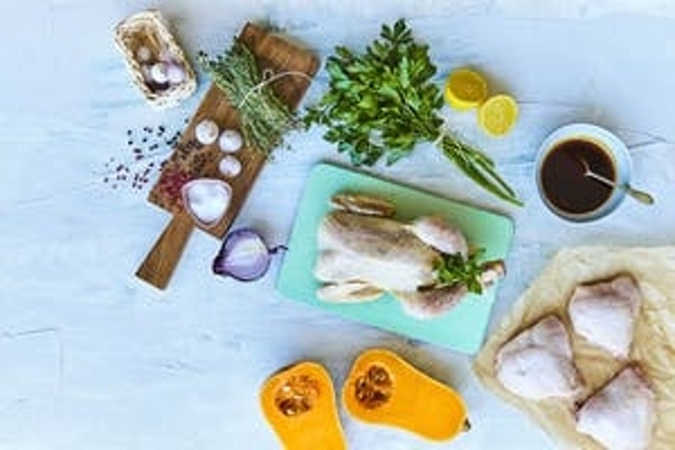 Bord med hel kylling, urter, hvitløk, rødløk og sitron.
