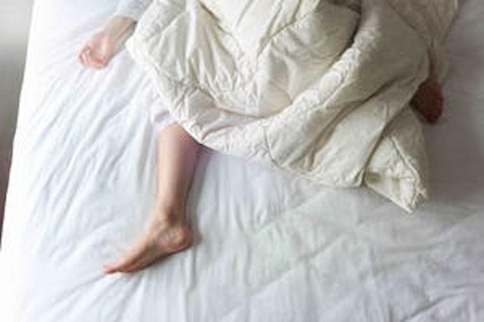 Kvinna sover med täcke
