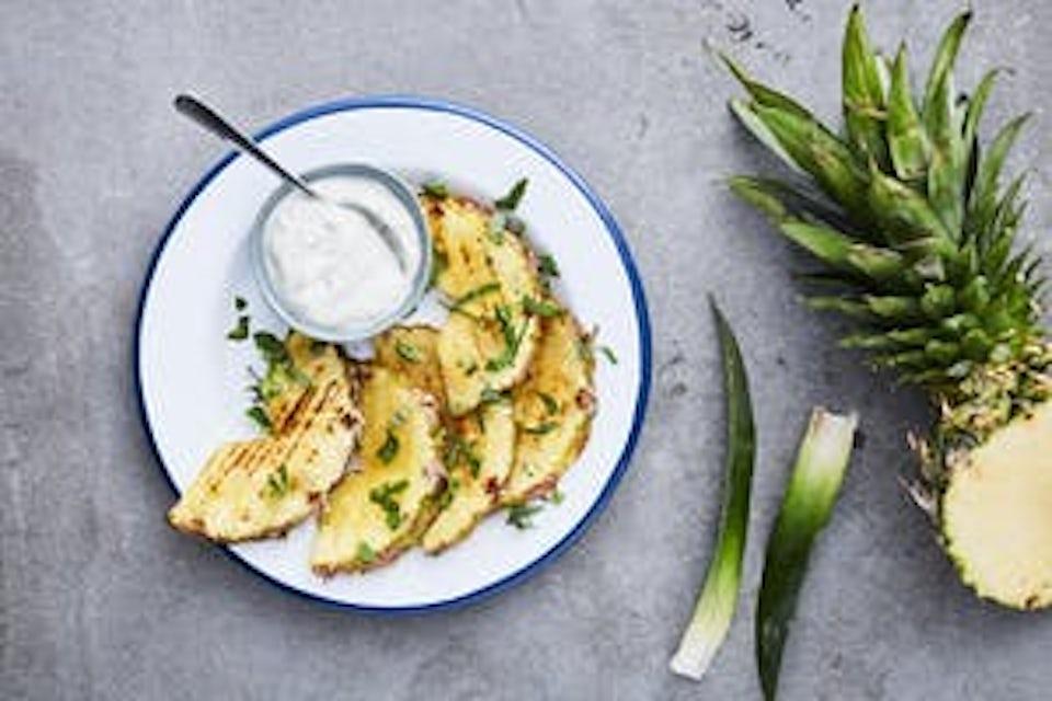 Tallerken med ananas og vaniljekrem i skål.