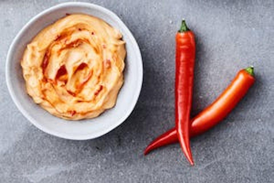 Skål med chilimajonäs och två röda chilifrukter