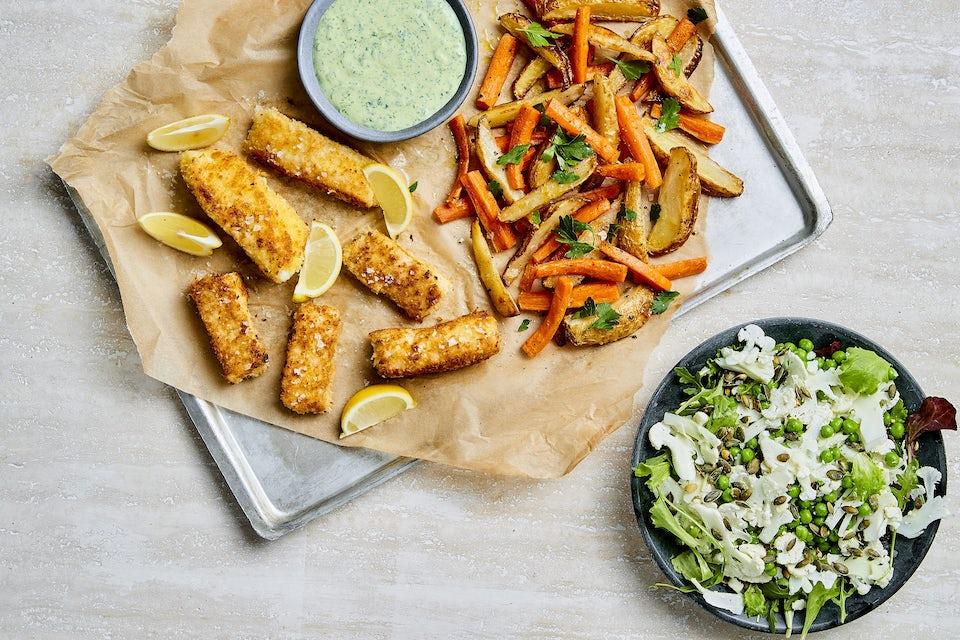Fad med stegt fisk, gulerod, kartofler og dressing, samt skål med salat af blomkål