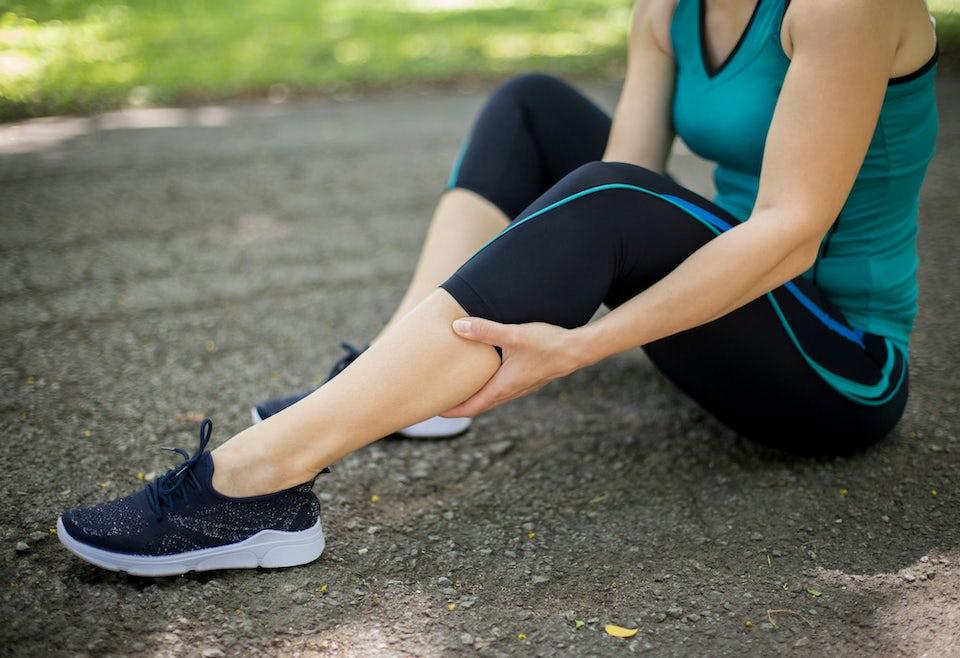 Kvinne sitter på bakken, krampe i leggen under trening