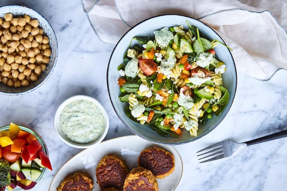 Tallerken med frikadeller, tallerken med pastasalt, tallerken med kikærter, tallerken med grøntsager og skål med dressing.