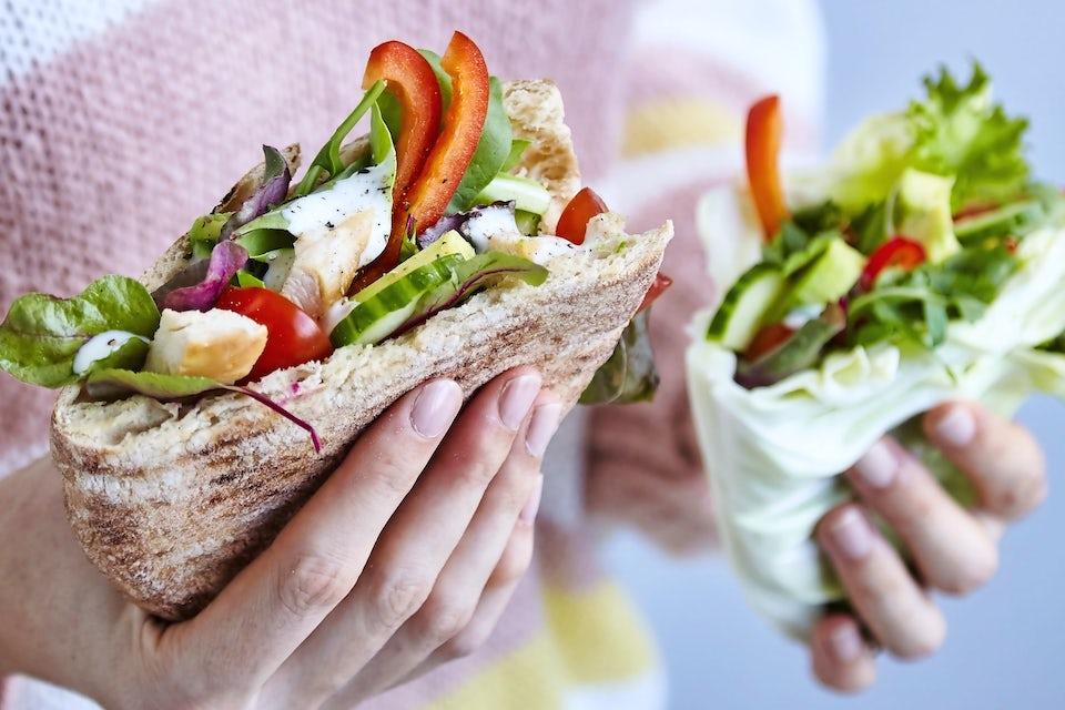 Hænder der holder to pitaer med grøntsager og kylling