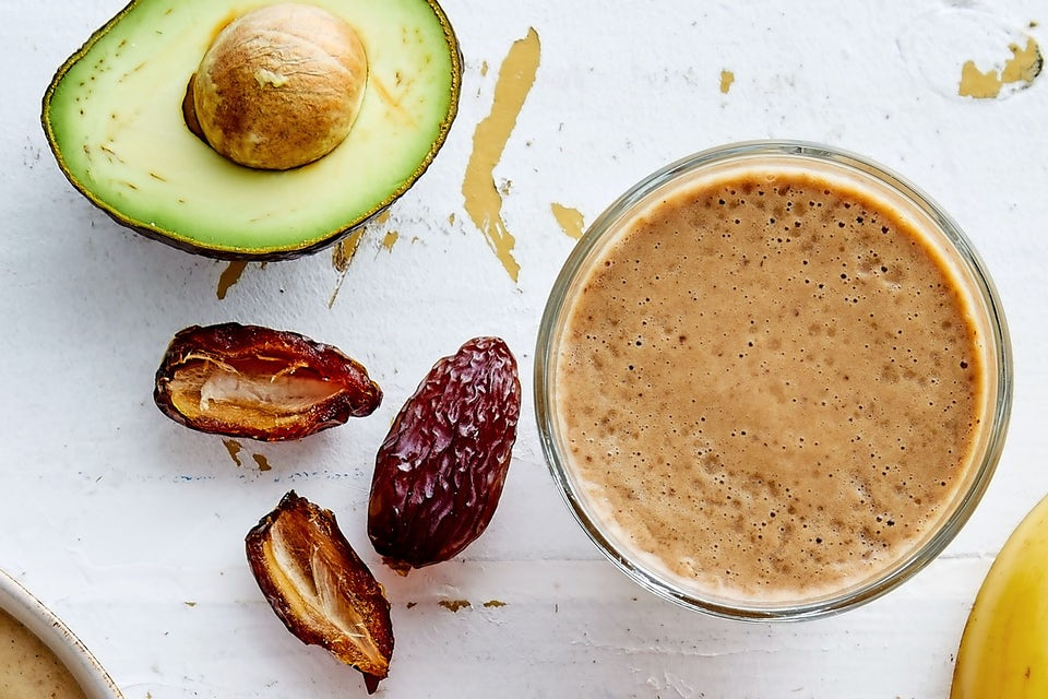 Glas med iskaffe och avokado och dadlar