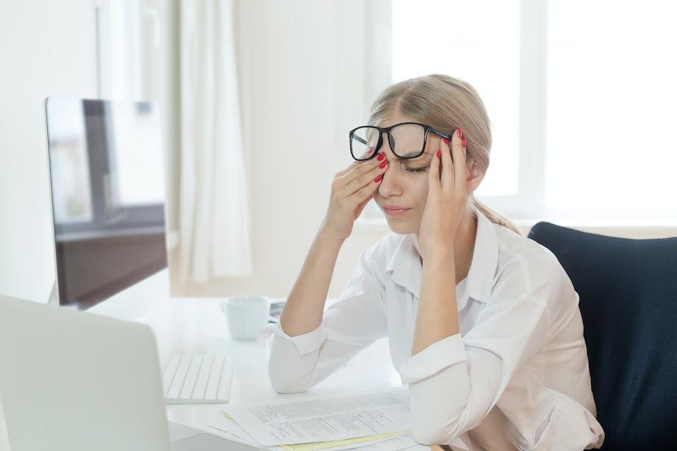 Väsynyt nainen toimistopöydän äärellä