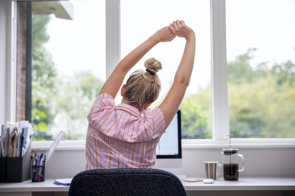 Kvinne strekker ut på kontoret