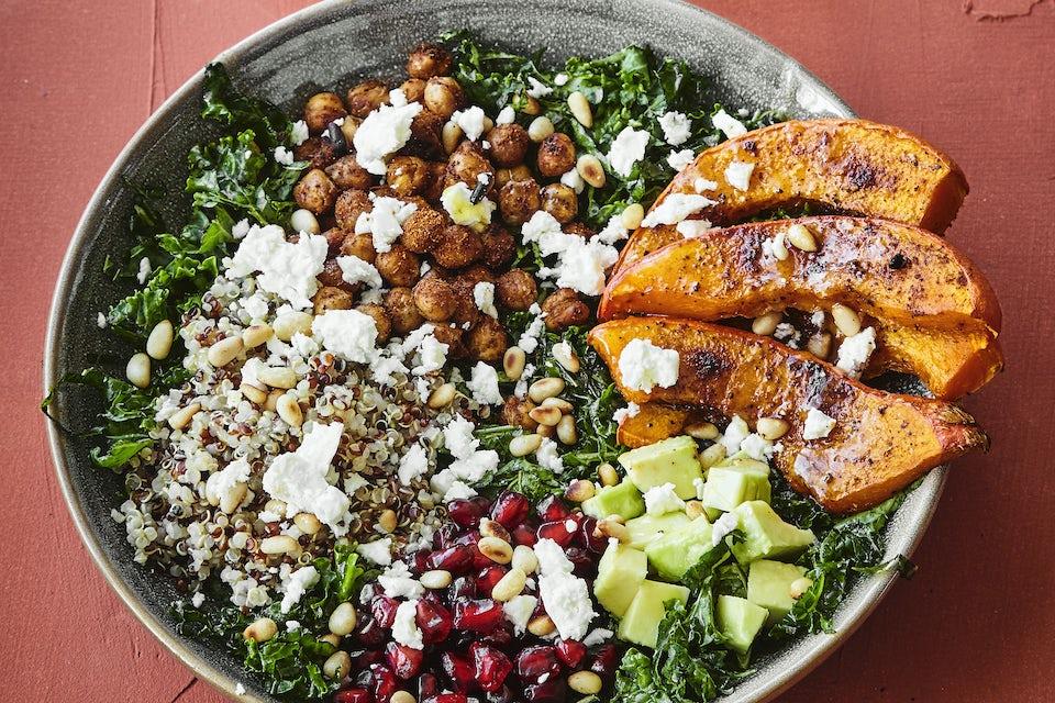 Tallerken med salat med gresskar, avokado, granateple, feta, pinjekjerner og grønnkål