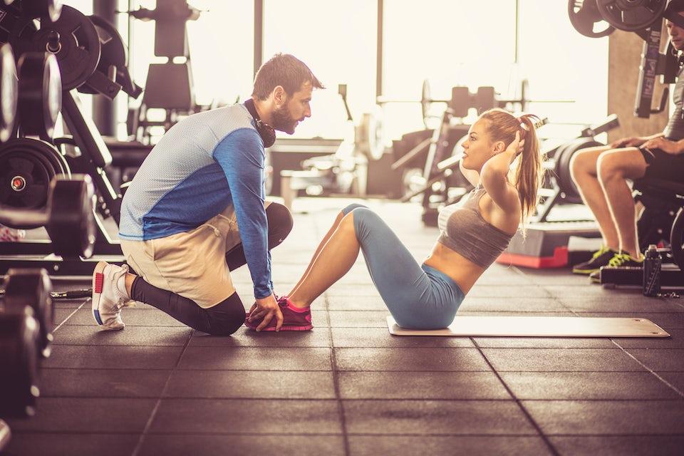 Kvinde laver mavebøjning med personlig træner