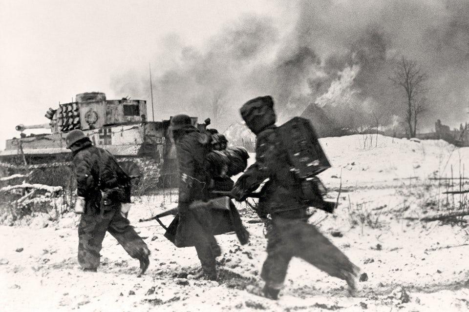 Östfronten 1944. Tyska grenadjärer i snö med utbränd Tiger stridsvagn i bakgrunden.